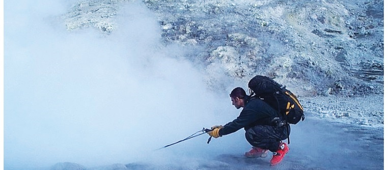 man near hot spring takes measurement using a long probe.