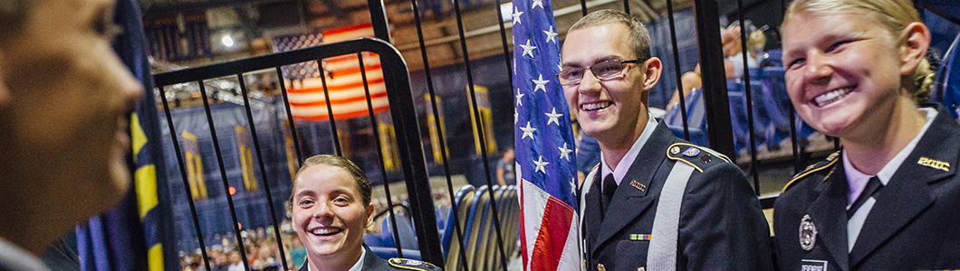 Three students in Air Force ROTC uniform, one holding the American flag, smile at Brick Breeden Fieldhouse.