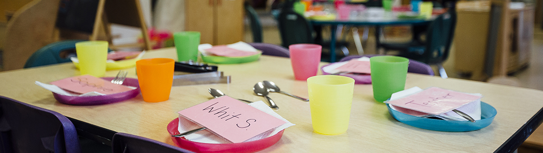 A table with children's plastic cutlery on it, as well as name tags.