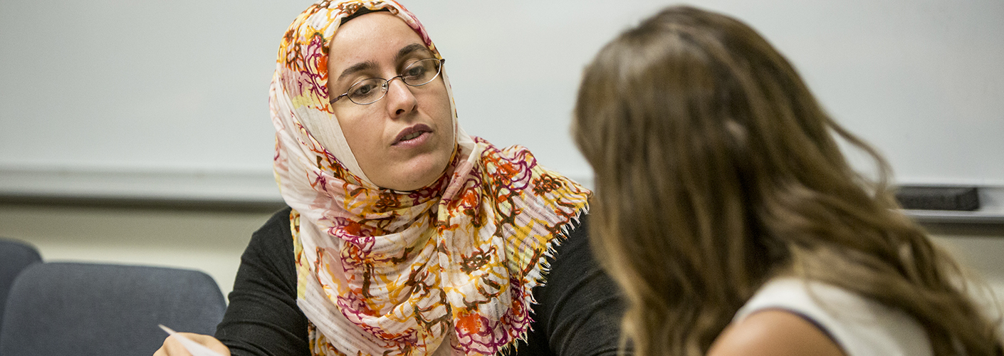 A woman in hijab and glasses consults with a student.