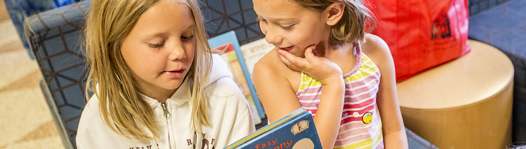 Two young students read a picture book.
