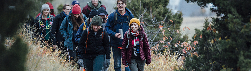 A group of male and female students hike on a trail.