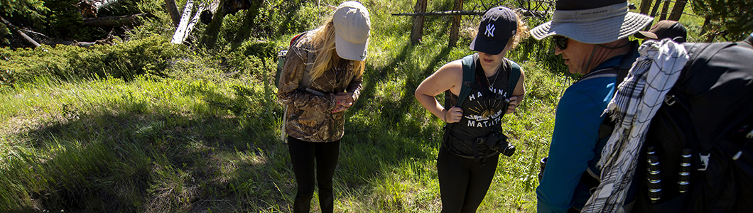 Three female scientists on a summer ecosystem survey study a waterway.