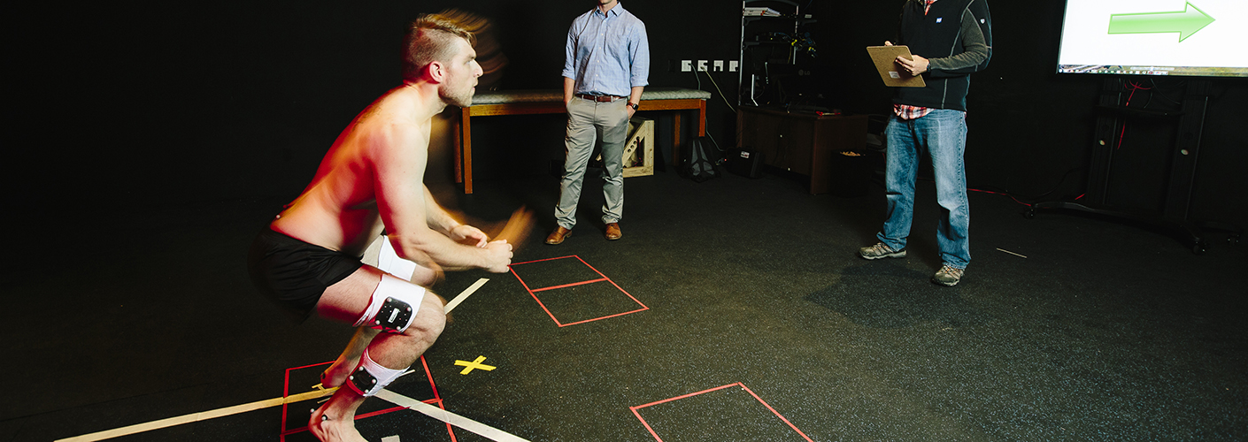 A young man with a series of sensors on him stands in front of researchers, ready to jump.
