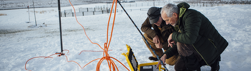 Researchers examine equipment readings in a winter field