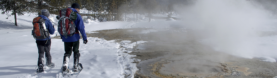 Two people snowshoe past a steaming creek in winter.
