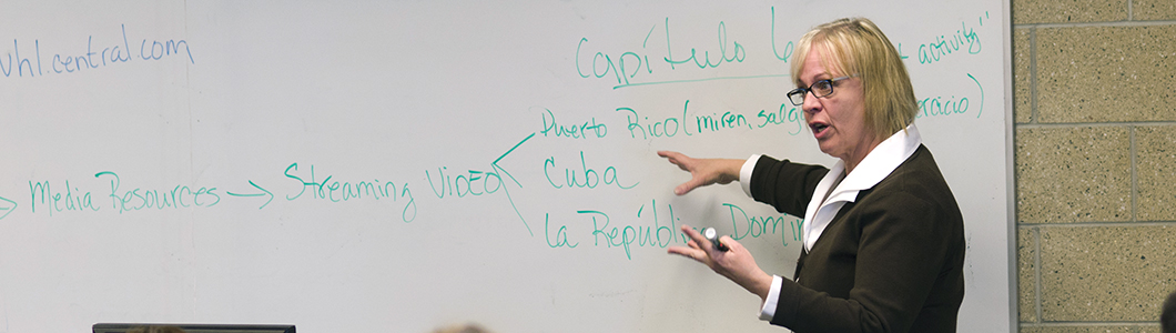 A professor gestures towards a series of Latin American countries on a whiteboard.
