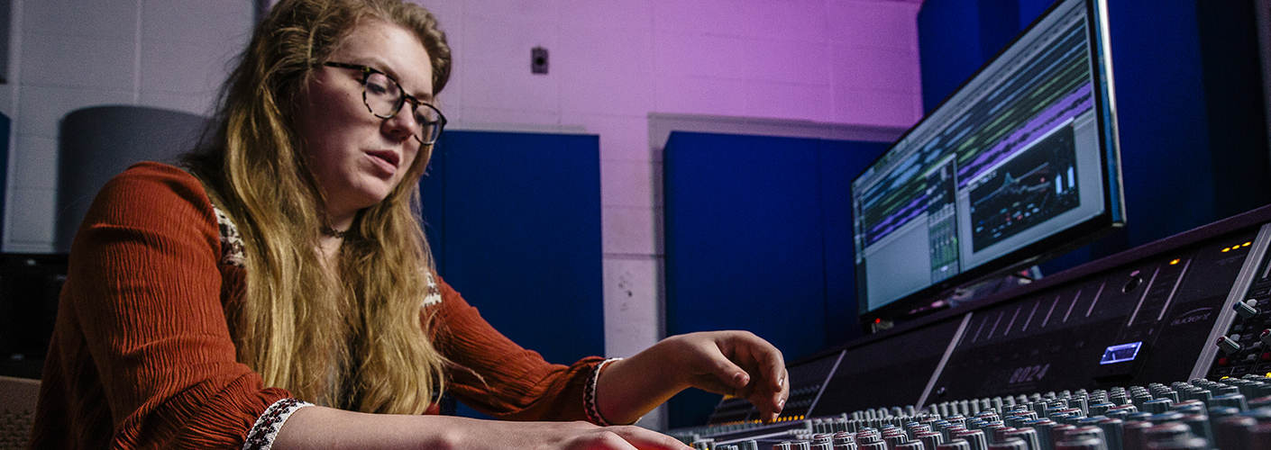 A young woman adjusts the dials on a sound mixing board, a computer screen in the background running sound editing software.