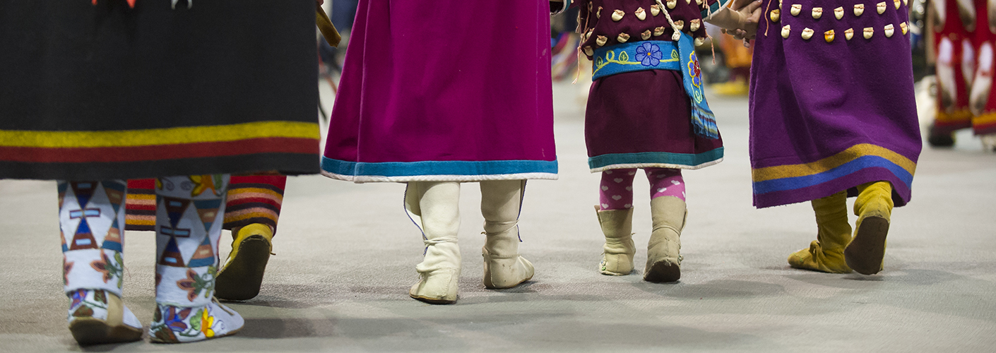A line of three women and a toddler-aged girl, all in traditional American Indian dress at a pow-wow, walk towards the festivities.