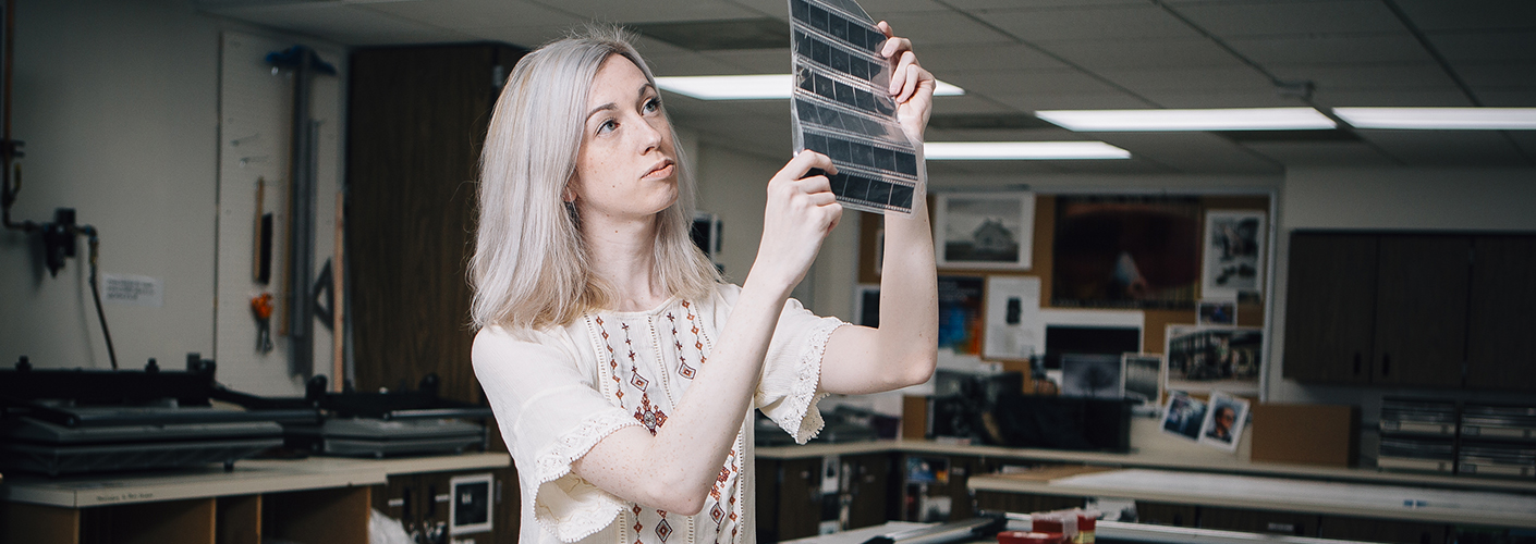 A young woman inspects a sheet of developed film negatives.