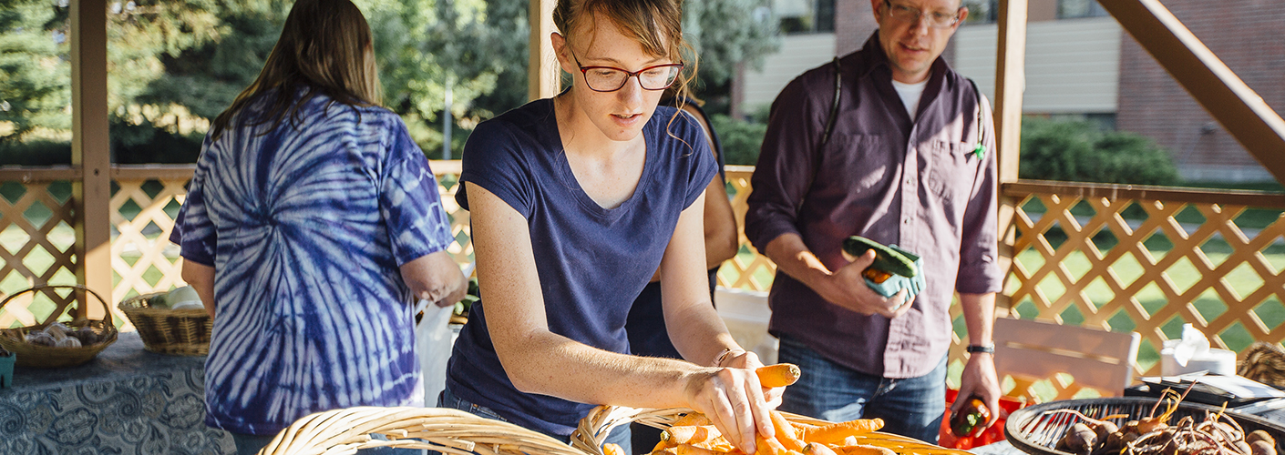 A young woman in glasses arranges carrots in a farmer's market stall, while a man with produce in his hands looks on.