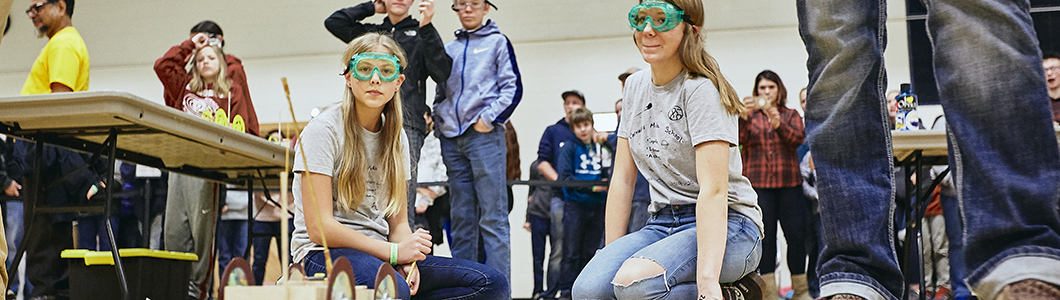 A group of students wearing goggles observe an experiment.