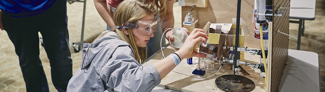 A young woman with safety goggles inspects a student's project.