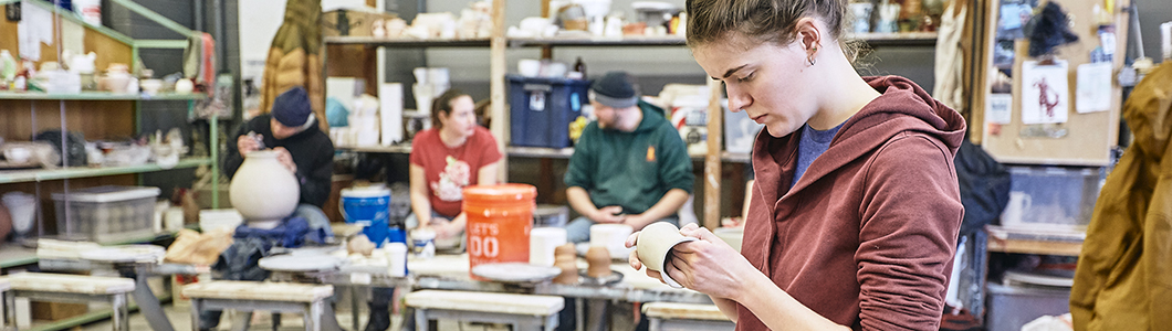 A group of students labor over pottery in a clay studio.