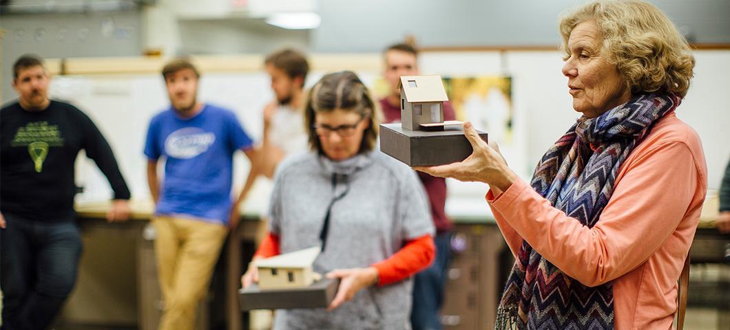 Professors critique projects in a studio.