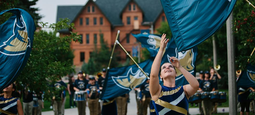 The Spirit of the West Color Guard throws flags in front of Montana Hall.