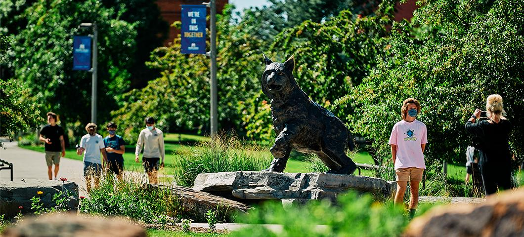 A student has their photo taken in front of Spirit the Bobcat.