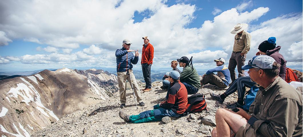 Students sitting on top of a mountain during a field expedition.