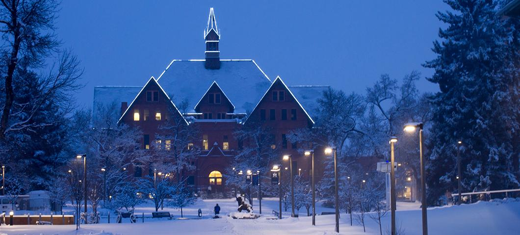 Montana Hall in winter during twilight.