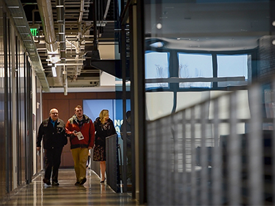 Three people walk down the hallway in Asbjornson Hall.