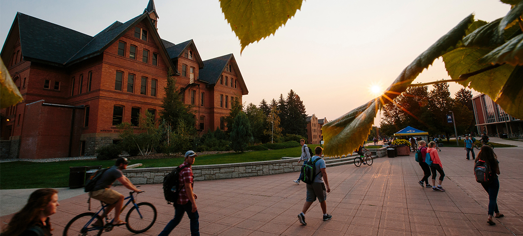 Students walk in front of Montana Hall during sunrise.