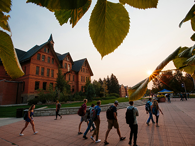 Students walk in front of Montana Hall during sunrise
