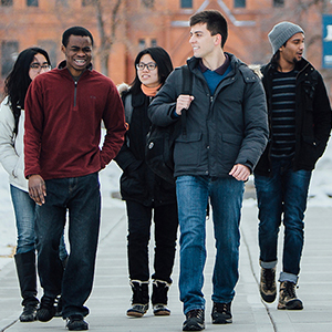 Group of students walking in front of Montana Hall in winter.