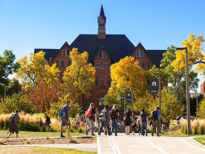 Students walking in front of Montana Hall in fall.