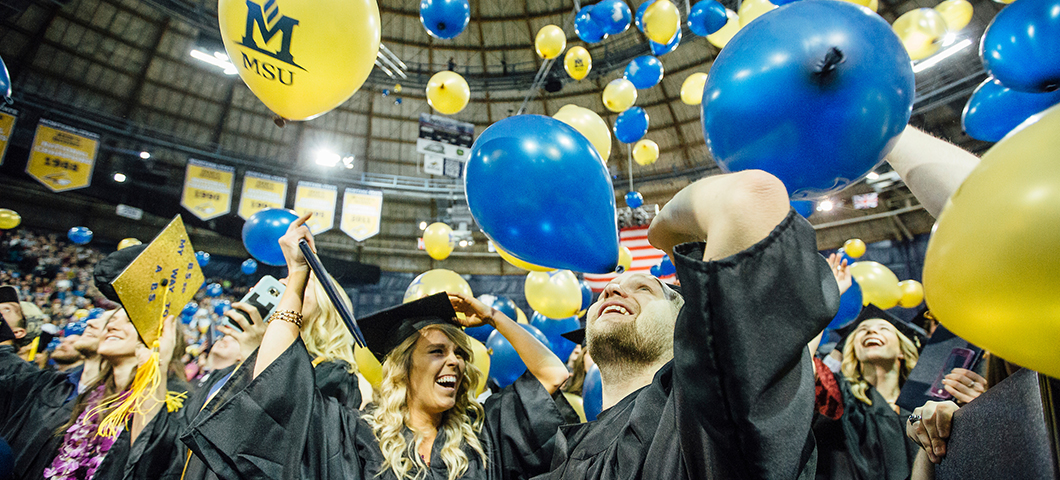 Students at graduation with blue and gold balloons.