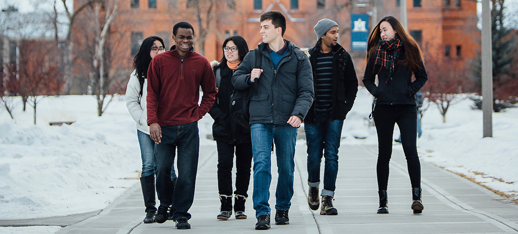 A group of students walks in front of Montana Hall in winter.