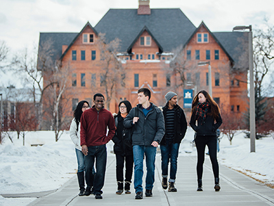 Students walk in front of Montana Hall in the snow.