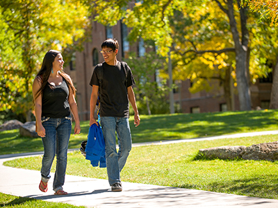 Two students walk on campus in the fall.