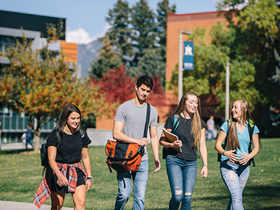 A group of students walk on campus in fall.
