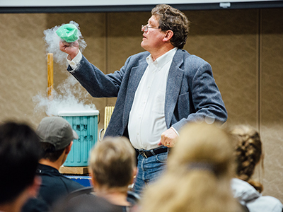A professor holds a beaker in front of a sample class.