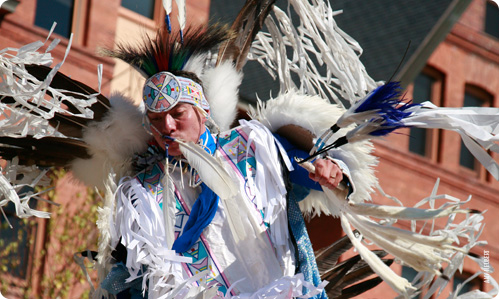 A Native American dances in front of Montana Hall