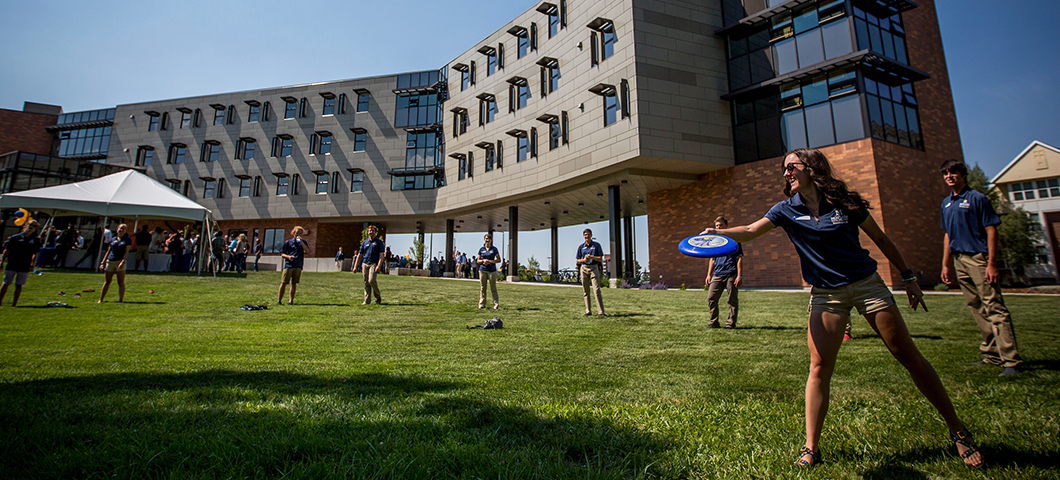 Students play frisbee in front of Yellowstone Hall during summer.