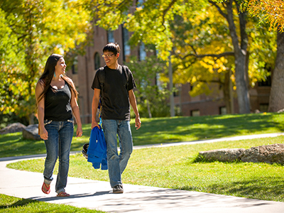 Two students walk on campus in fall.