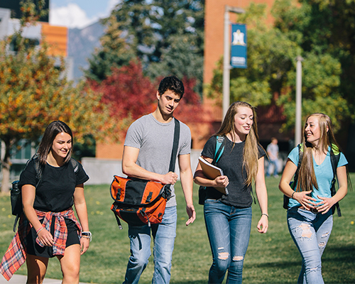 A group of students walk across campus during fall.