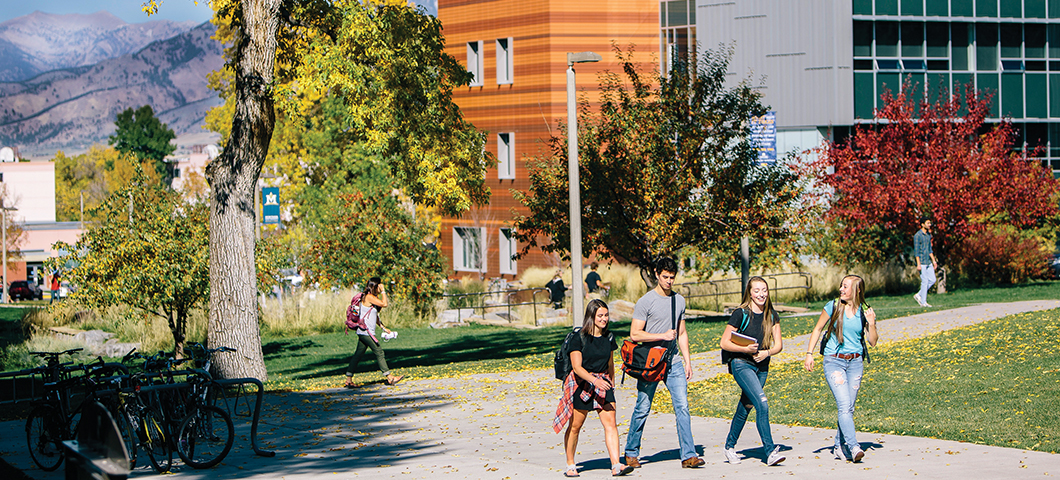 A group of students walk in front of Jabs Hall in fall.
