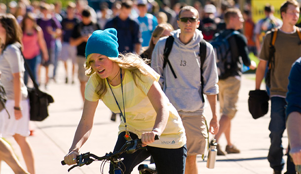 A student rides ehr bike on campus