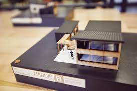 miniture building model sitting on top of a black binder