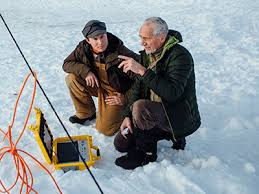 two men discussing project while crouching on the snow