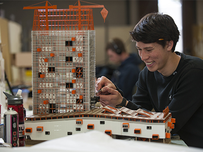 Student tinkering with architecture model