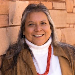 Photo shows Zonnie Gorman, a Navajo woman with tan skin, brown eyes, and hair that is showing her wisdom in grey strands, smiling with a brick wall behind her.