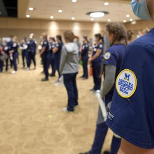 "A group of people wearing scrubs and masks stand in a large room. ""Montana State University College of Nursing"" can be seen on one person's arm badge."