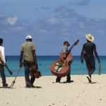 Image of musicians on a beach.
