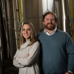 Katherine and Jeremiah Johnson standing next to tanks in their Great Falls, Montana brewery.