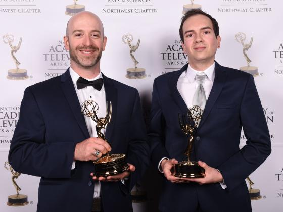 Two men in suits posing for a photo with Emmy awards | Jeremiah Slovarp