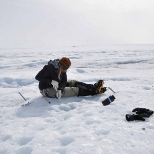 Dr. Christine Foreman sitting on a sheet of ice digging for microbes.