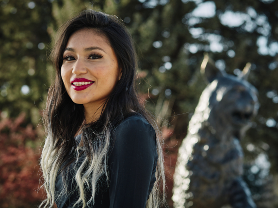 A woman in a black top, smiles for a portrait outside near a bobcat statue and evergreen foliage. | MSU Photo by Adrian Sanchez-Gonzalez